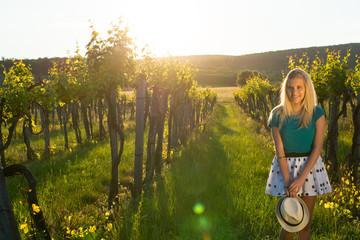 Beautiful girl standing in hat between grapes.