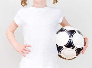 Little girl in white T-shirt with ball. Front view.