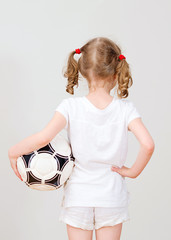 Little girl in white T-shirt with ball. Back view.
