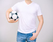 Man in white t-shirt with ball. Grey background.