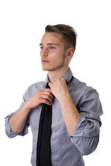 Elegant young man wearing and adjusting neck-tie