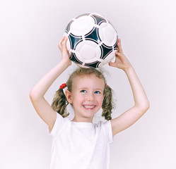 Little girl with ball smiling.