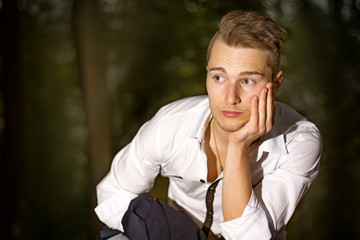 Serious young man outdoors in park at night