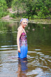 Beautiful woman in dress standing in pond