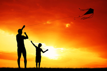 father and son with kite at sunset