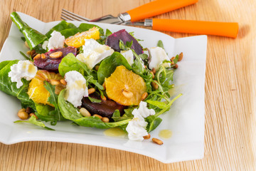 fresh salad with roasted beetroot, white cheese, orange and pine