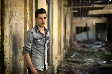 Handsome young man in abandoned, run down building