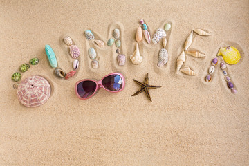 Word summer made from sea shells, with sunglasses and star fish,