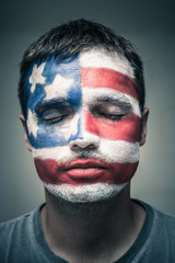 Man with USA flag on face and closed eyes