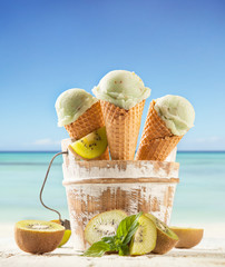 Ice cream scoops in cones with blur beach