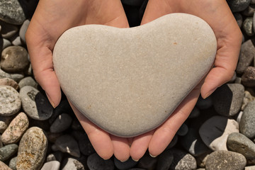 Female hands holding a heart-shaped stone