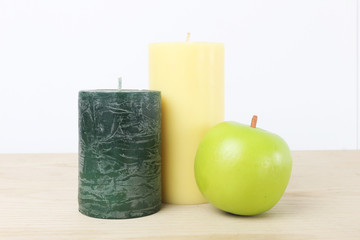 candle with fruit on wood table and a white background.