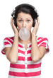 Woman with earphones blows out a bubble gum, isolated on white