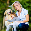 Mother and daughter with pet sitting on the green grass