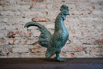 Metal Chicken Sculpture on the wood table with the brick wall