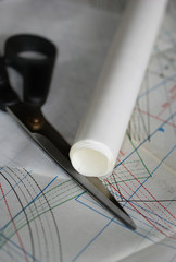 Sewing drawing, scissors and roll of tracing paper laying on the