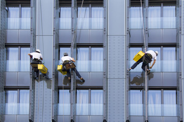 Three climbers wash windows