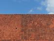 Rotbraunes Ziegeldach vor blauem Himmel mit Wolkenbildung