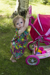 Girl of 1 year old is walking in a garden.