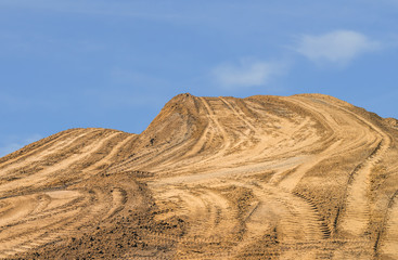 Construction dirt pile, tire tracks, blue sky background