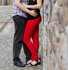 Happy young couple in love at the stone wall