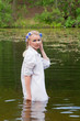 Beautiful woman in white standing in pond