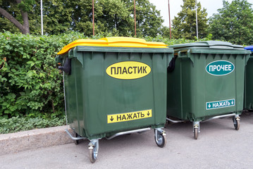 Green dumpsters on a city street with inscription on russian