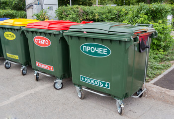 Green dumpsters on a city street