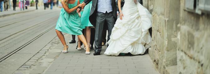Groom, bride and bridesmaids walking street.