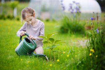 Cute little girl watering plants in garden
