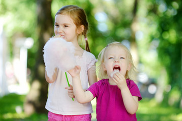 Adorable little sisters eating candy-floss