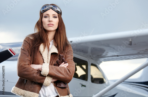 Fototapeta Portrait of young beautiful woman pilot in front of airplane.