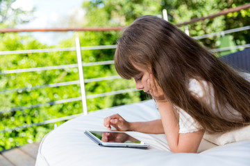 Girl playing with tablet on patio