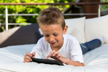 Boy lying down with his tablet