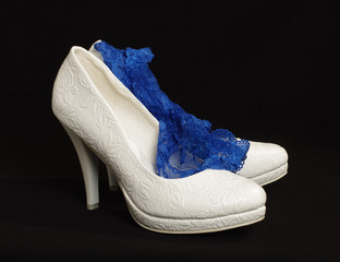 White bride shoes with sexy blue garter isolated