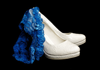 Blue wedding garter on the pair of bridal shoes