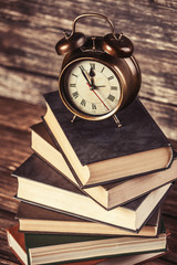 Alarm clock and books on wooden table.