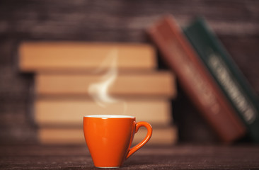 Books and cup of coffee on wooden background.