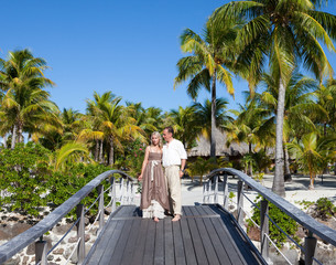 Loving couple on wooden bridge on the tropical island