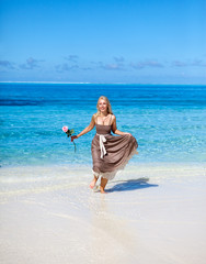 young beautiful woman  with a rose on sand at the sea edge