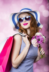 Redhead girl with shopping bags and flowers on pink background.