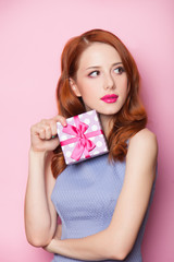Redhead girl with gift on pink background.