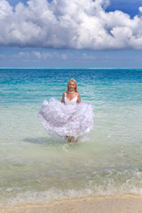 beautiful woman in dress of bride runs on waves of sea
