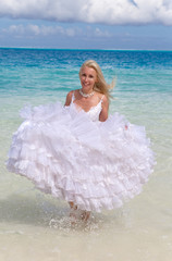 young beautiful woman in dress of bride runs on waves of the sea