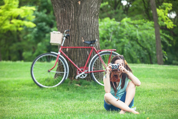 Funny girl with camera and bike in the park