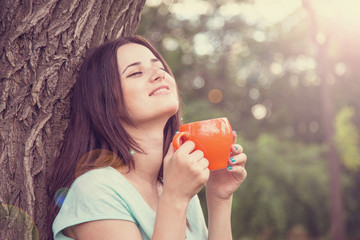 Brunette girl with cup of coffee near tree in the park.