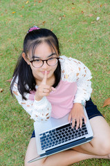 Lovely girl with a laptop on the grass