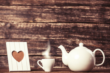 Teapot and cup of coffee with frame on wooden table.