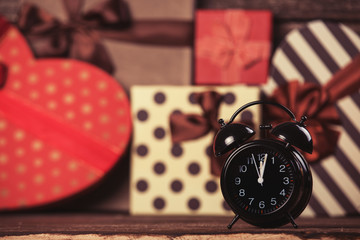 Alarm clock and gifts on background.