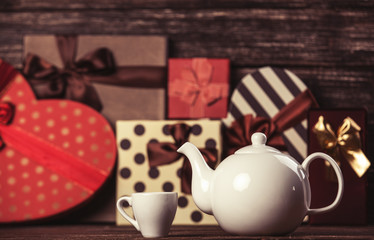 Teapot and gifts on background.